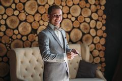 A smiling Groom is prepared on a wedding day, puts on a jacket and straightens the sleeves. Classical business clothes. For work or office. Businessman in gray royalty free stock photography
