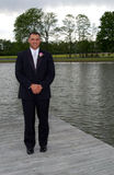Smiling groom standing by lake. Smiling groom stood on pier by lake stock photos