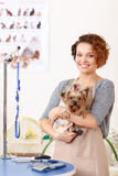 Smiling groomer holding a Yorkshire terrier Stock Photos