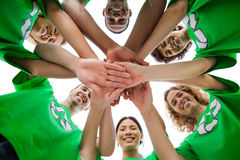Smiling group of activists piling up their hands Stock Photography