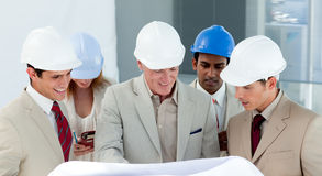 Smiling group of architect examining blueprints Stock Photo