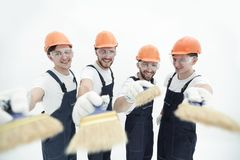 Smiling group of builders with a paint brush. Closeup.smiling group of builders with a paint brush.isolated on white stock photo