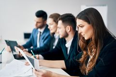 Smiling group of business people sitting in row together at table in modern office stock images