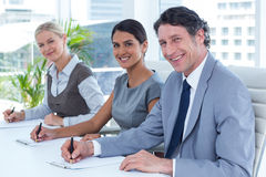 Smiling group of business people taking notes Royalty Free Stock Images