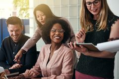 Smiling group of diverse businesspeople working in an office stock images