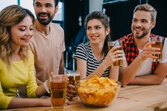 Smiling group of friends with beer and bowl of chips sitting at bar counter during watch of. Soccer match royalty free stock images