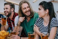 smiling group of friends drinking beer and watching football match stock photography