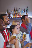 Smiling group of friends having beer while watching match Royalty Free Stock Image