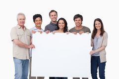 Smiling group holding blank sign together. Against a white background Stock Photography