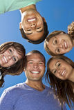 Smiling group of Multi-racial Young Adults. Five young ethnically-diverse adults happily smile as they huddle together showing friendship and a strong bond of Royalty Free Stock Image