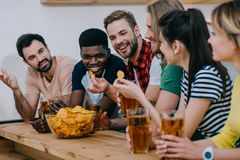 smiling group of multicultural friends eating chips drinking beer and watching soccer match stock photo