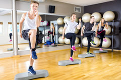 Smiling group raising legs on step platforms at fitness gym Royalty Free Stock Photos
