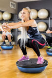 Smiling group training squats on half ball at fitness gym. Happy and smiling people in workout team doing squats on half ball in a fitness gym class. Core muscle Stock Image