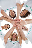 Smiling group of volunteers piling up their hands. On white background Stock Images