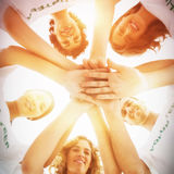 Smiling group of volunteers stacking hands. On white background Stock Photos