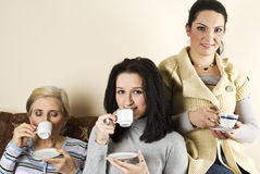 Smiling group of women at coffee. Smiling three women friends sitting in a couch and enjoying a hot drink together,see more in People on couch Royalty Free Stock Images