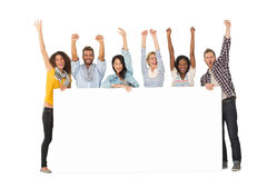 Smiling group of young friends showing large poster and cheering Royalty Free Stock Image
