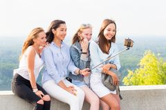 Smiling group of young women taking a selfie in nature royalty free stock image