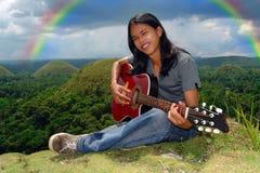Smiling guitar player u rainbow Stock Photography