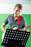 Smiling Guitarist Performing While Looking At Stock Images