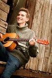 Smiling guitarist played by guitar in lost village Stock Images
