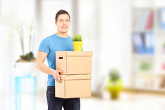 Smiling guy carrying removal boxes during moving royalty free stock photo