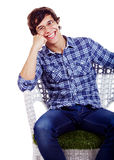 Smiling guy on chair with hand under cheek Royalty Free Stock Image