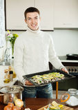 Smiling guy cooking trout fish in roasting pan Royalty Free Stock Photo