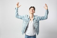 Smiling guy dark-haired guy dressed in a white t-shirt and a denim jacket stands and raises his hands up on the white royalty free stock photo