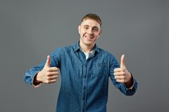 Smiling guy dressed in a jeans shirt keeps both thumbs up in the studio on the gray background stock photos