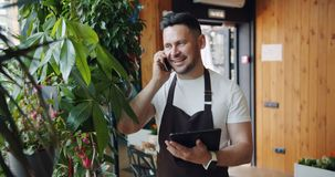 Smiling guy florist speaking on mobile phone and holding modern tablet at work. Smiling guy florist in apron is speaking on mobile phone and holding modern stock video footage