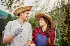 Smiling guy and girl gardeners in a straw hats look to each other in garden on a sunny day. royalty free stock photo