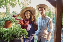 Smiling guy and girl gardeners in a straw hats are standing next royalty free stock photo