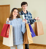 Smiling guy and girl holding purchases in hands. At home Royalty Free Stock Images