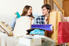 Smiling guy and girl looking at purchases. In home Stock Image