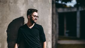 Smiling guy in glasses near wall. Portrait of smiling calm bearded hipster in glasses looking aside while standing in front of concrete wall outdoors on sunny Stock Images