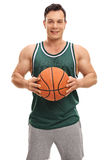 Smiling guy in a green jersey. Posing with a basketball isolated on white background stock images