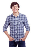 Smiling guy with hands in pockets. Portrait of young hispanic man wearing glasses, blue shirt with rolled up sleeves and jeans standing with hands in pockets and Stock Photography