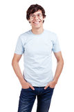 Smiling guy with hands in pockets. Portrait of young hispanic man wearing glasses, blue t-shirt and jeans standing with hands in pockets and smiling isolated on Royalty Free Stock Photography