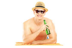 Smiling guy with hat lying on a beach towel and drinking cold be Royalty Free Stock Photography