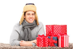 A smiling guy with hat and neckwear lying on a carpet near prese Stock Photo