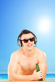 Smiling guy with headphones and sunglasses drinking beer Stock Photo