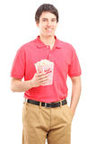 Smiling guy holding a popcorn box Royalty Free Stock Photography
