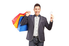 A smiling guy holding shopping bags and credit card Royalty Free Stock Photos
