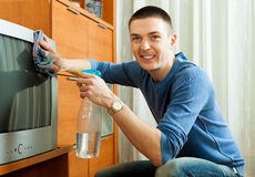 Smiling guy in homecleaning TV at living room Stock Photo