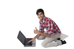 Smiling guy on laptop thumbs up Royalty Free Stock Photography