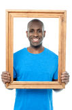 Smiling guy looking through picture frame Stock Image