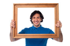 Smiling guy looking through picture frame Royalty Free Stock Image