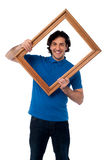 Smiling guy looking through picture frame Royalty Free Stock Photo
