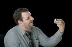 Smiling guy looks at vodka shot. Mature smiling short haired guy looks at vodka shot on black background Stock Image